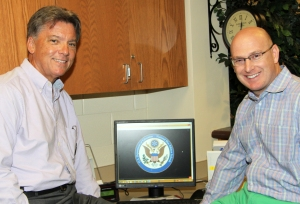 Haysville USD 261 Superintendent Dr. John Burke (left) and Oatville Elementary School Principal Shane Dent watched the computer monitor as they waited for the 2014 National Blue Ribbon School announcement to be streamed live from Washington, D.C.